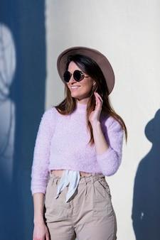 Frontowy widok piękna modna młoda kobieta jest ubranym okulary przeciwsłonecznych i kapeluszową pozycję na ulicie podczas gdy pozujący w słonecznym dniu