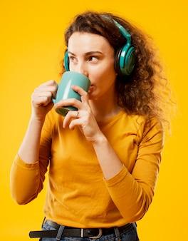 Frontowy widok pije od zielonej filiżanki kobieta