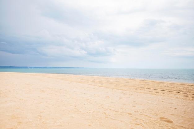 Frontowy widok plaża z piaskiem i chmurami