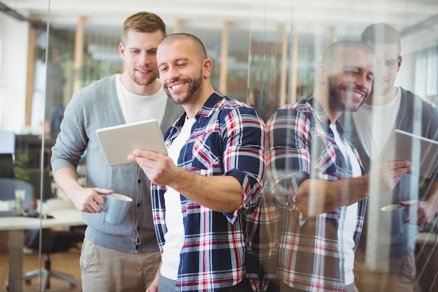 Frontowy widok pokazuje cyfrową pastylkę kolega biznesmen