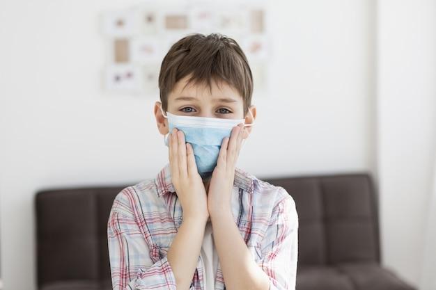 Frontowy widok pozuje dziecko podczas gdy będący ubranym medyczną maskę