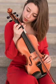 Frontowy widok pozuje kobieta podczas gdy trzymający skrzypce