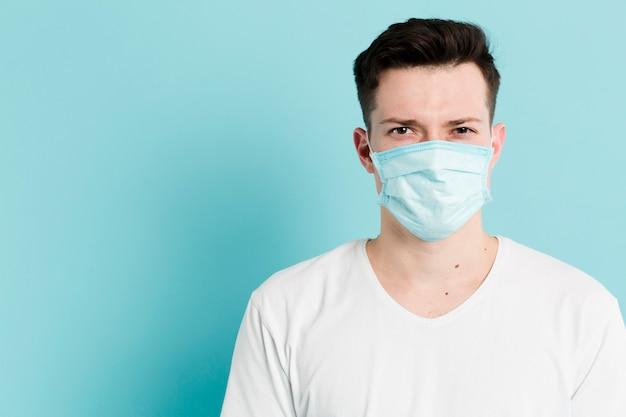 Frontowy widok pozuje mężczyzna podczas gdy będący ubranym medyczną maskę