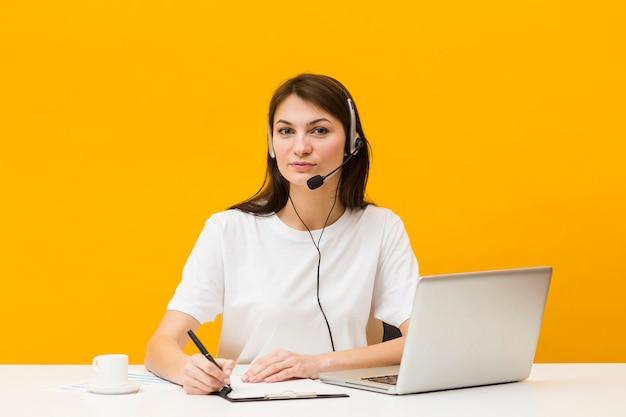 Frontowy widok pozuje przy jej biurkiem kobieta podczas gdy będący ubranym słuchawki