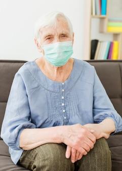 Frontowy widok pozuje stara kobieta podczas gdy będący ubranym medyczną maskę