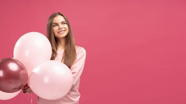 Frontowy widok pozuje z balonami smiley kobieta