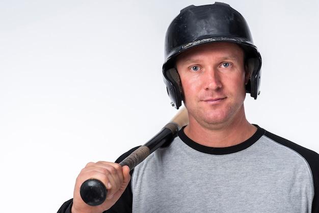 Frontowy widok pozuje z hełmem i nietoperzem gracz baseballa
