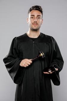 Frontowy widok pozuje z młoteczkiem męski sędzia