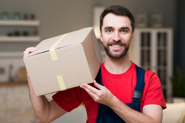 Frontowy widok pozuje z pudełkami doręczeniowy mężczyzna