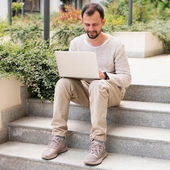 Frontowy widok pracuje na laptopie na krokach mężczyzna