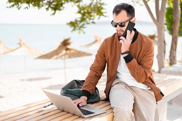 Frontowy widok pracuje na laptopie przy plażą mężczyzna
