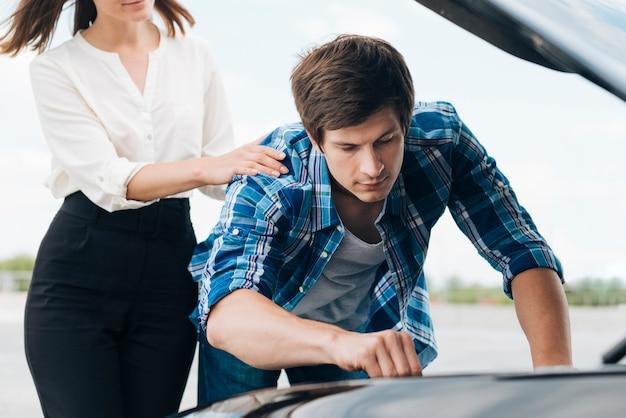 Frontowy widok pracuje na samochodowym silniku mężczyzna