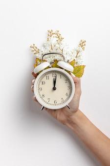 Frontowy widok ręczny zegar z kwiatem i liśćmi