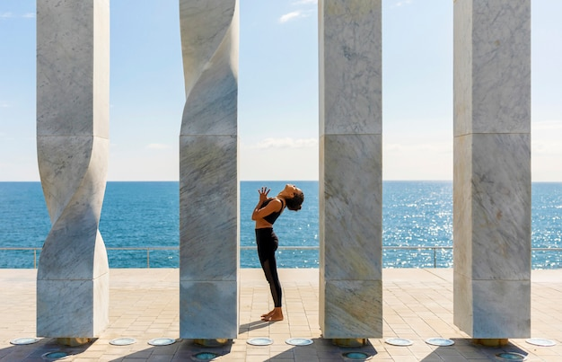 Frontowy widok robi joga na nadmorski amerykanin afrykańskiego pochodzenia kobieta