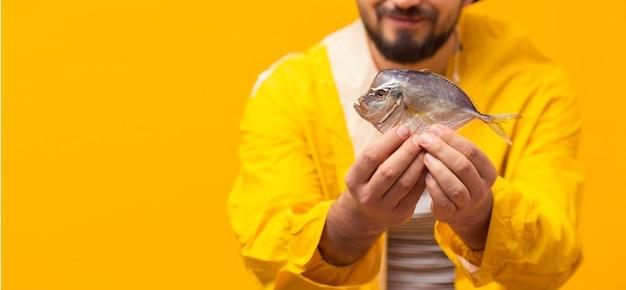Frontowy widok rybaka mienia chwyt z kopii przestrzenią