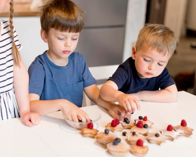 Frontowy widok śliczni rodzeństwa gotuje w domu