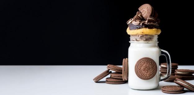 Frontowy widok słój deser z ciastkami i pączkiem
