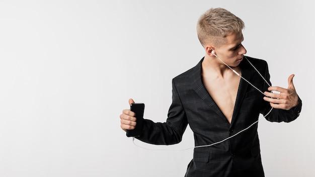 Frontowy widok słucha muzyka na hełmofonach z kopii przestrzenią męski tancerz