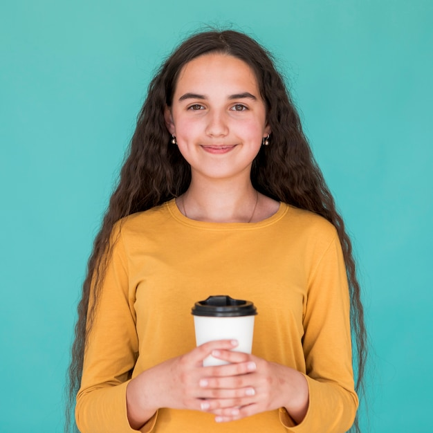 Frontowy widok smiley dziewczyna trzyma jej napój