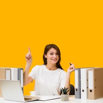 Frontowy widok smiley kobieta ma pomysł przy jej biurkiem