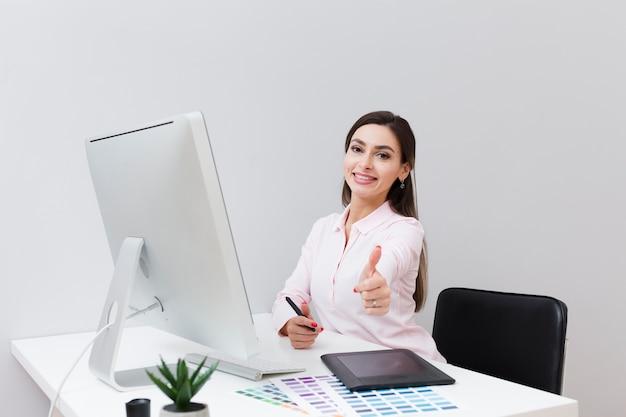 Frontowy widok smiley kobieta przy biurkiem daje aprobatom