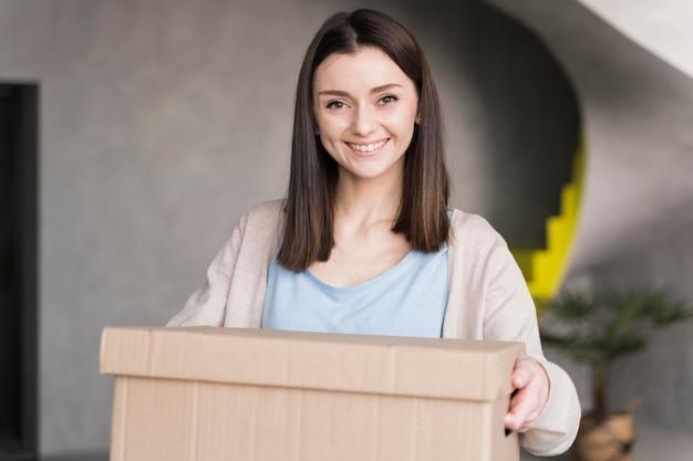 Frontowy widok smiley kobiety mienia karton