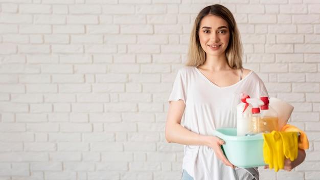 Frontowy widok smiley kobiety mienia wiadro z cleaning rozwiązaniami