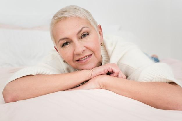 Frontowy widok smiley starsza kobieta w łóżku
