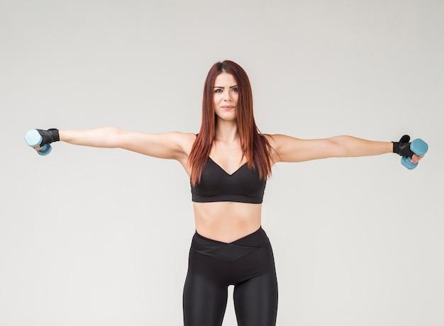 Frontowy widok sportowa kobieta ćwiczy z ciężarami w gym ubiorze