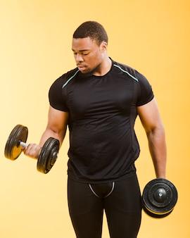 Frontowy widok sportowy mężczyzna mienie obciąża w gym stroju