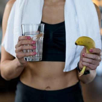 Frontowy widok sporty kobiety mienia banan i szkło woda