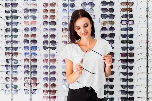Frontowy widok sprawdza okulary przeciwsłonecznych kobieta