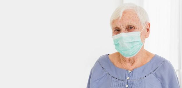 Frontowy widok stara kobieta z medyczną maski i kopii przestrzenią