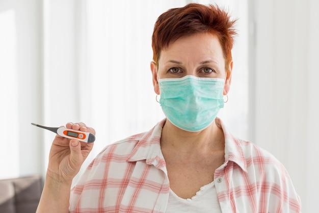 Frontowy widok starsza kobieta z medycznym maskowym mienie termometrem