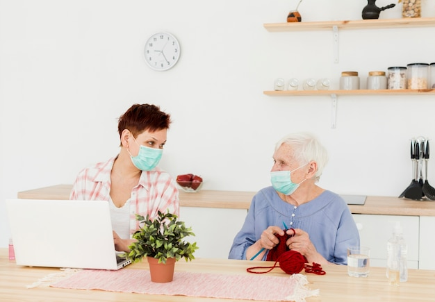 Frontowy widok starsze kobiety jest ubranym medyczne maski w domu podczas gdy robić aktywność