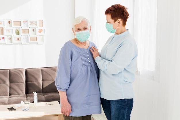Frontowy widok starsze kobiety jest ubranym medyczne maski w domu