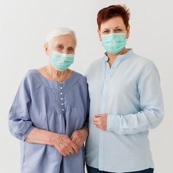 Frontowy widok starsze kobiety z medycznymi maskami dalej