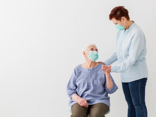 Frontowy widok starsze kobiety z medycznymi maskami i kopii przestrzenią