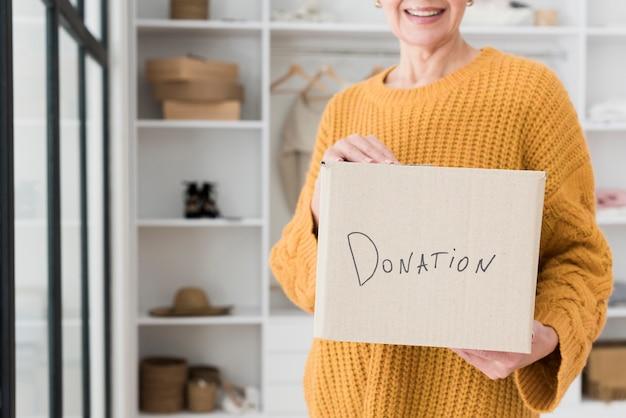 Frontowy widok starszej kobiety mienia pudełko z darowizną