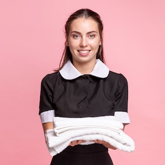 Frontowy widok szczęśliwa gosposia trzyma białych ręczniki