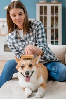 Frontowy widok szczotkuje jej psa kobieta