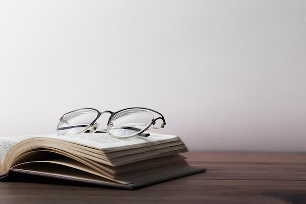 Frontowy widok szkła na otwartej książce na drewnianym stole