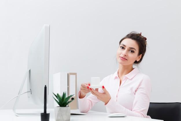 Frontowy widok trzyma filiżankę kawy przy biurkiem kobieta pracująca
