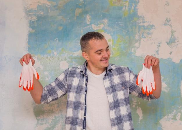 Frontowy widok trzyma rękawiczki i patrzeje mężczyzna