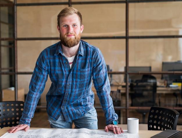 Frontowy widok uśmiechnięta biznesmen pozycja przed biurkiem