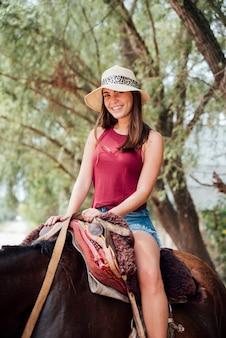 Frontowy widok uśmiechnięta kobieta jedzie konia