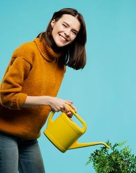 Frontowy widok uśmiechnięta kobieta z podlewanie puszką