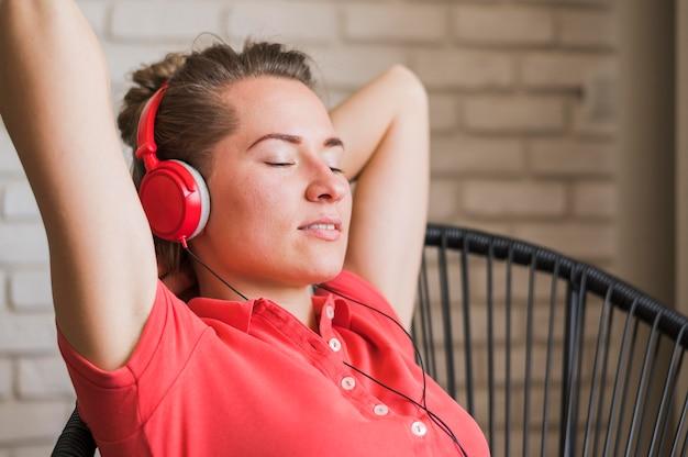 Frontowy widok uśmiechniętej kobiety słuchająca muzyka