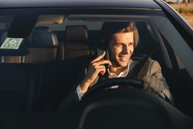 Frontowy widok uśmiechnięty bussinesman jedzie jego samochód w kostiumu