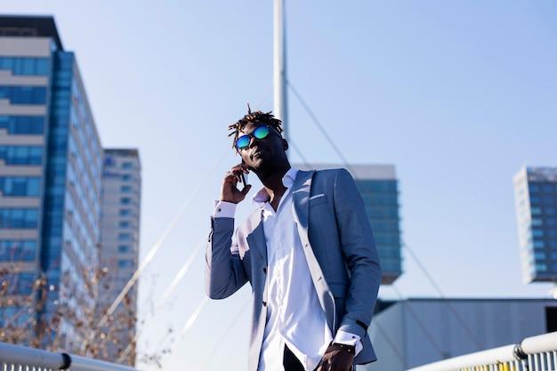 Frontowy widok uśmiechnięty młody czarnego afrykanina mężczyzna jest ubranym eleganckie ubrania stoi w ulicie podczas gdy używać telefon komórkowego outdoors w słonecznym dniu